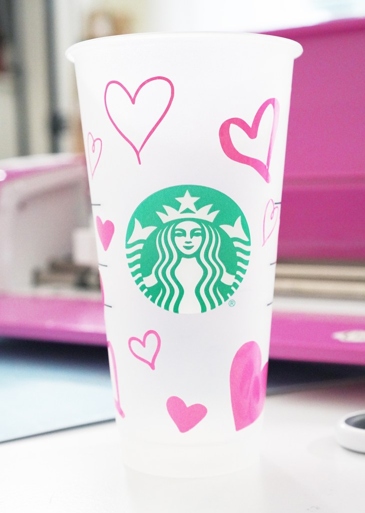Pink Color Changing Vinyl Hearts on Starbucks Plastic Cup in front of Cricut Machine