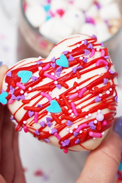 Hand holding Heart shaped Hot Chocolate Bomb for valentine's Day