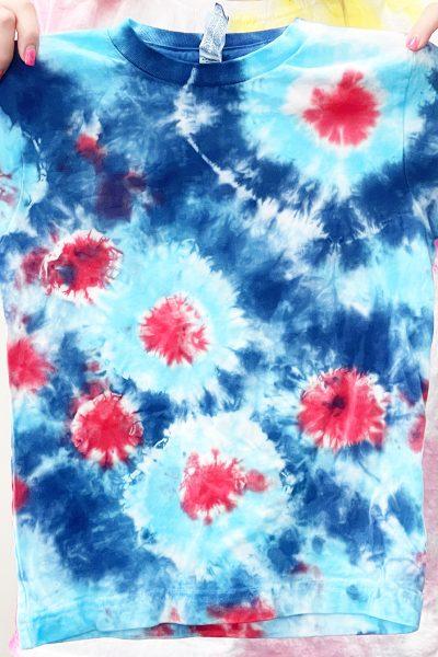 girl holding red white and blue fireworks sunburst tie dye shirt
