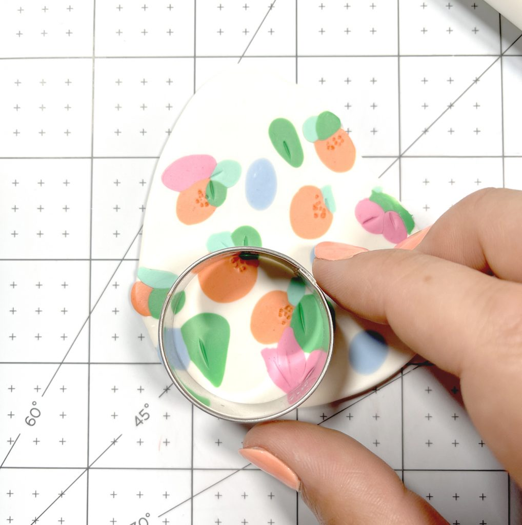 using circle cookie cutter on floral polymer clay slab to make earrings