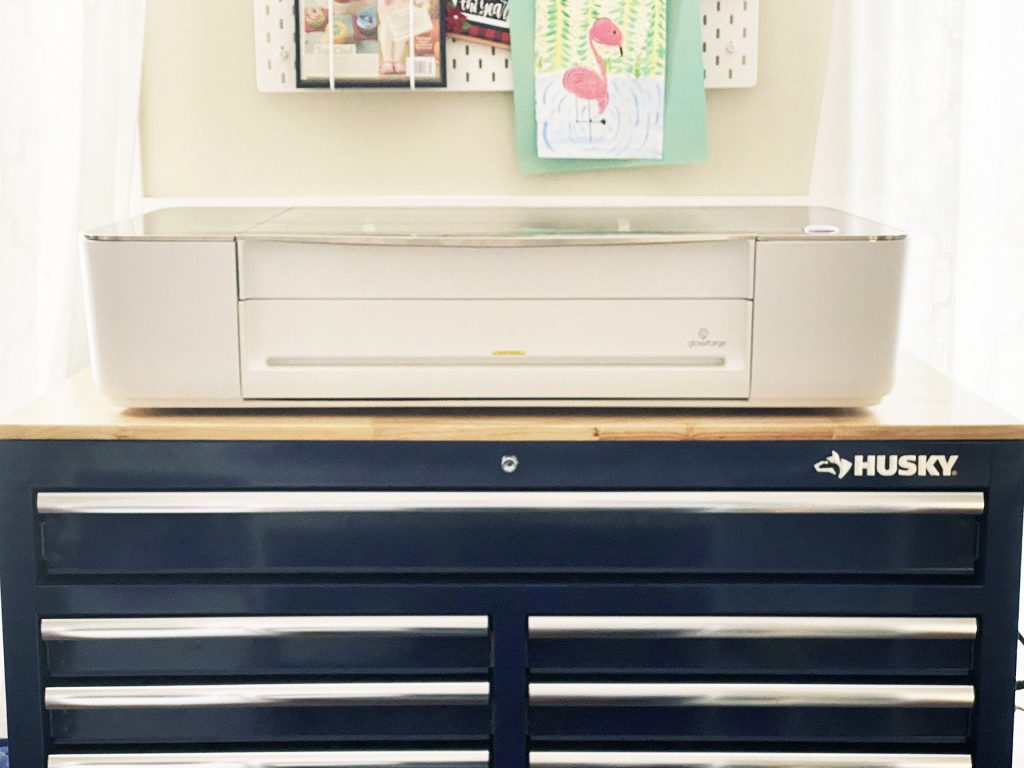 Glowforge 3d laser printer sitting on large husky blue workbench with drawers