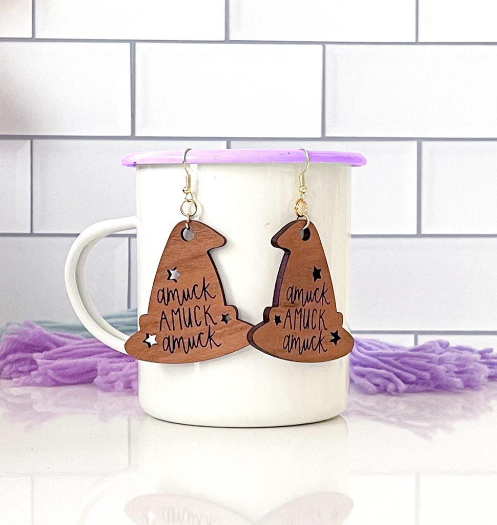 Laser Cut Wooden Halloween Earrings with Amuck Hanging on White Enamel Mug