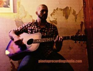 Blake playing originals on guitar