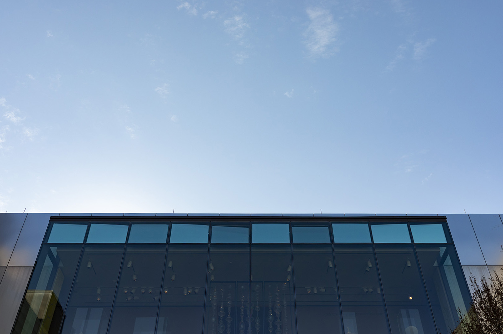 """Image of """"Cloud Text"""" taken from the ground level of the Chazen Museum of Art. The panels of the piece are reflecting the clouds in the sky with different shades of blue."""