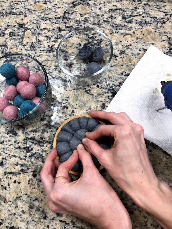 Hot gluing gray felt balls into place on wooden coaster - Pink Bows & Twinkle Toes