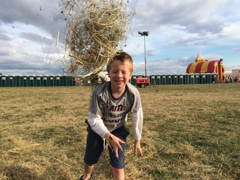 boy playing in hay