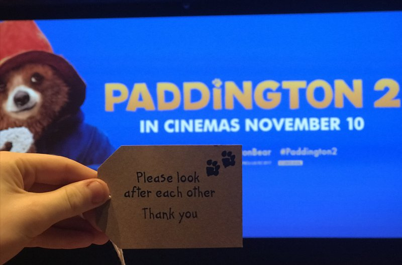 Paddington 2 cinema screen and luggage tag saying to look after each other
