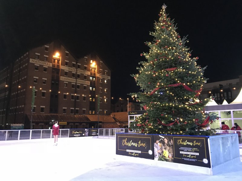 outdoor ice skating rink with Christmas tree in the middle, a skater in red and buildings in the background