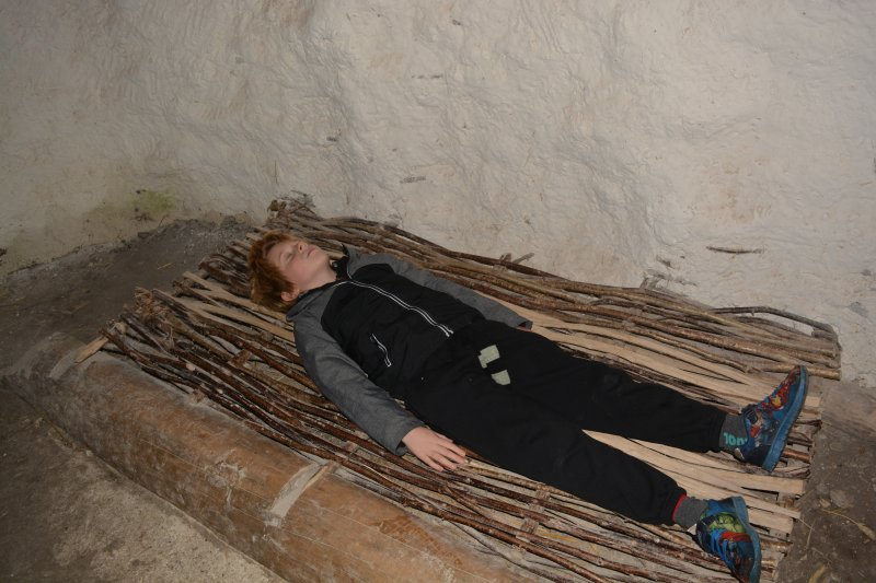 child lying on bed in Neolithic Houses at Stonehenge