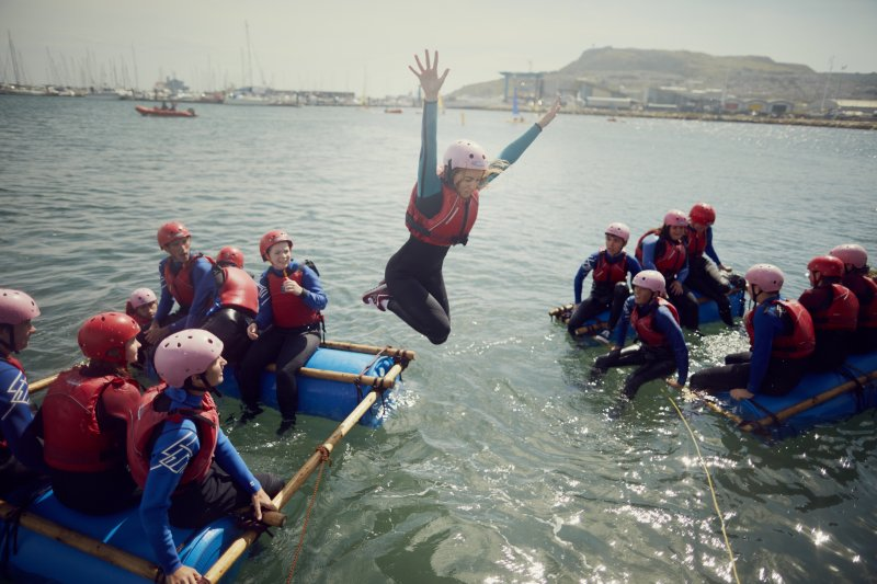 girl jumping from a boat into the water with ncs