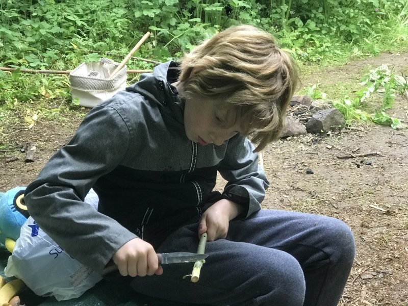 boy with knife cutting a stick at home education forest school