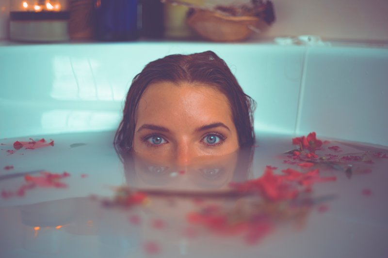 woman with bath tub so full it covers her nose and surrounded by red petals