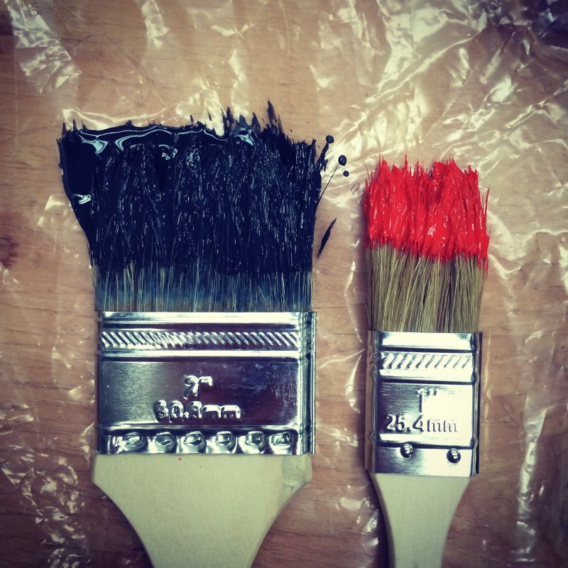 paint brushes one with blue on the end and the other with red