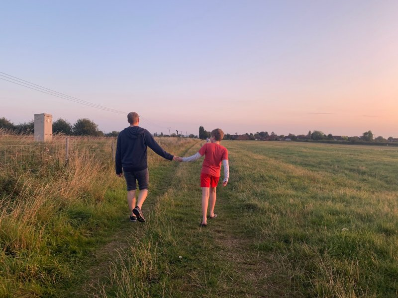 father and son holding hands on a field as the sun sets