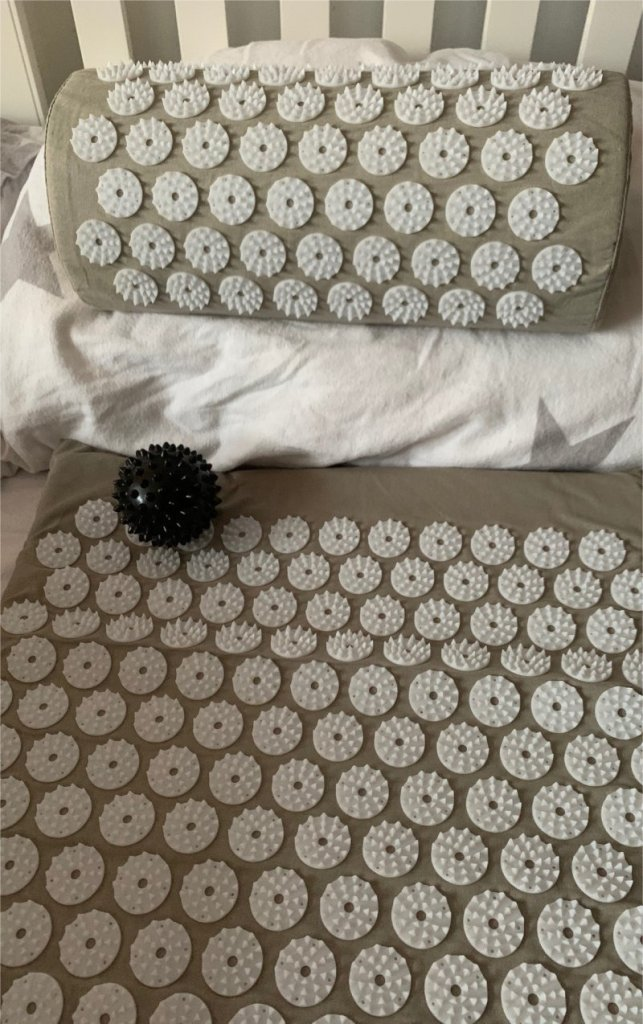 shakti mat on bed with extra pillow and massage ball