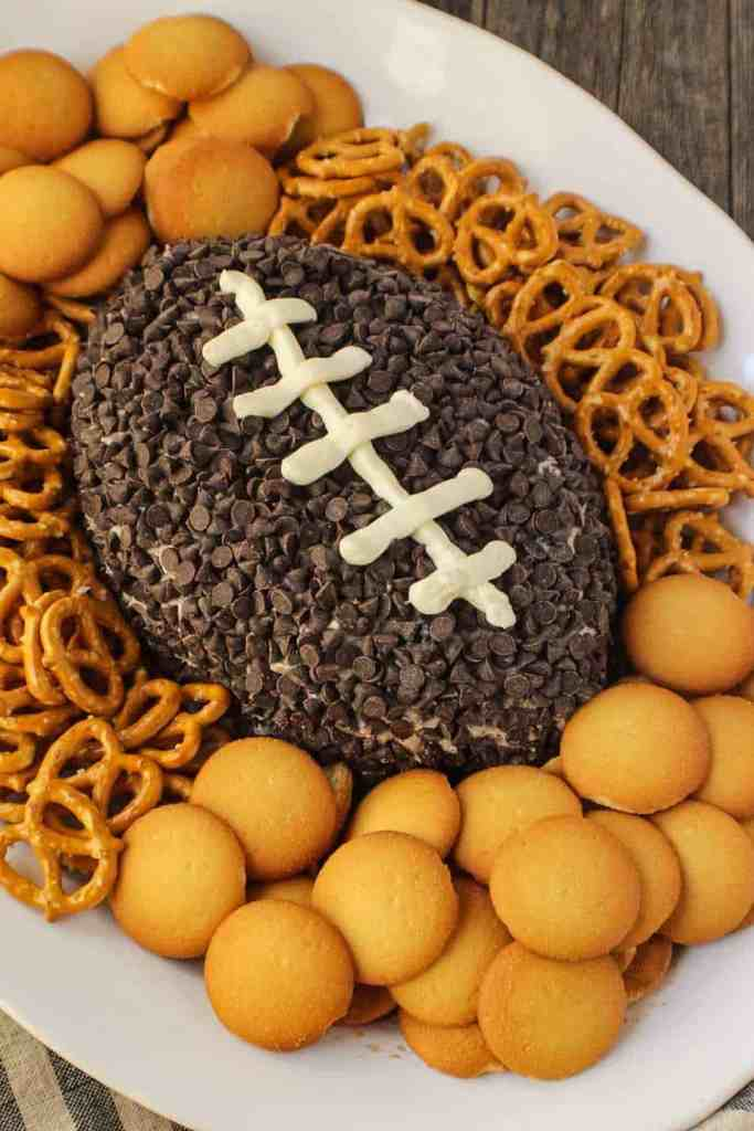 Cookies and cream cheese ball shaped and decorated to look like a football. sitting on a white serving platter with pretzels and vanilla wafer cookies around cheese ball.