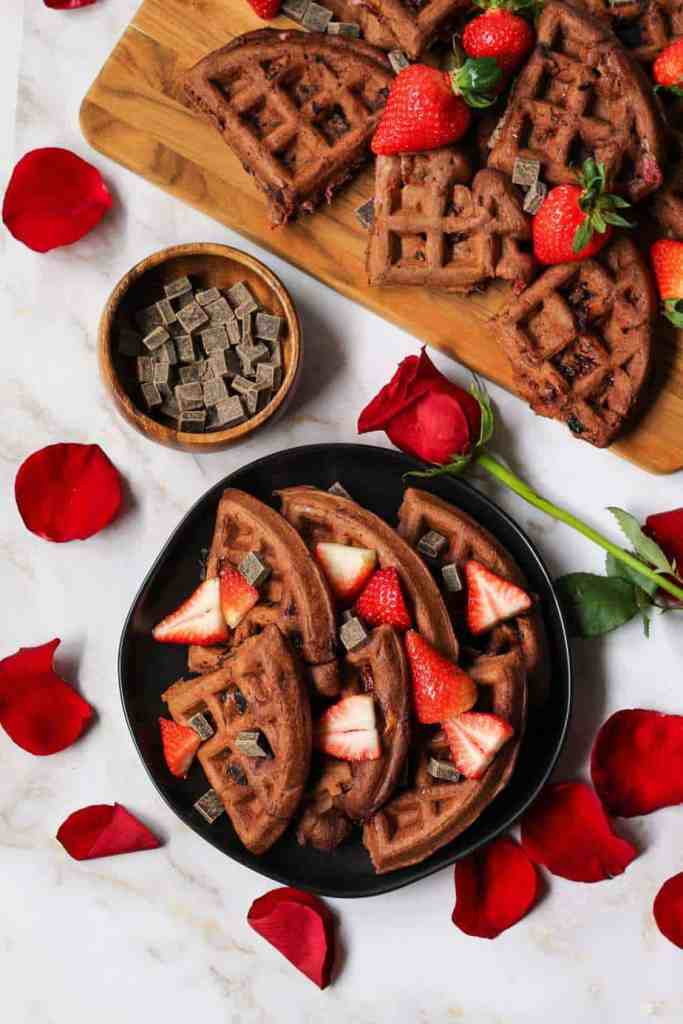 overhead shot of Double dark chocolate strawberry waffles topped with dark chocolate chunks, pancake syrup and sliced strawberries. Rose and rose petals scattered in shot.
