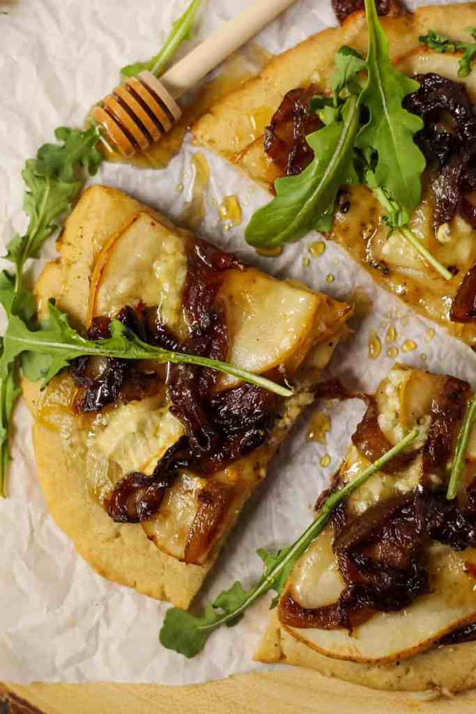 close up overhead shot of flatbread topped with sliced pears, caramelized onions and brie cheese. Garnished with arugula and honey. Flatbread is on top of parchment on a wooden serving board.