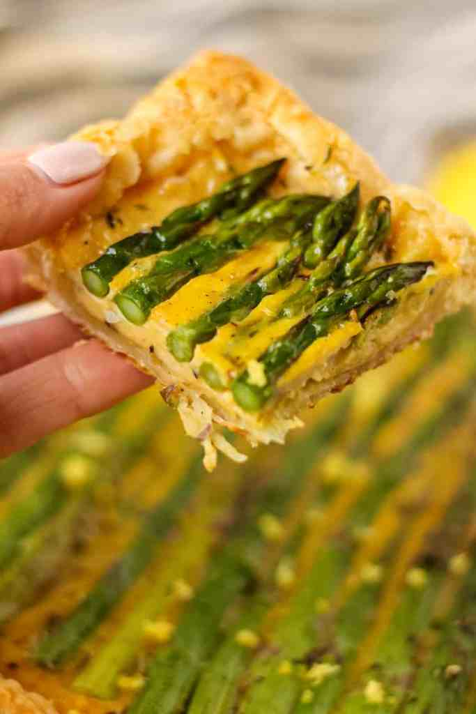 close up of slice of asparagus tart in hand.
