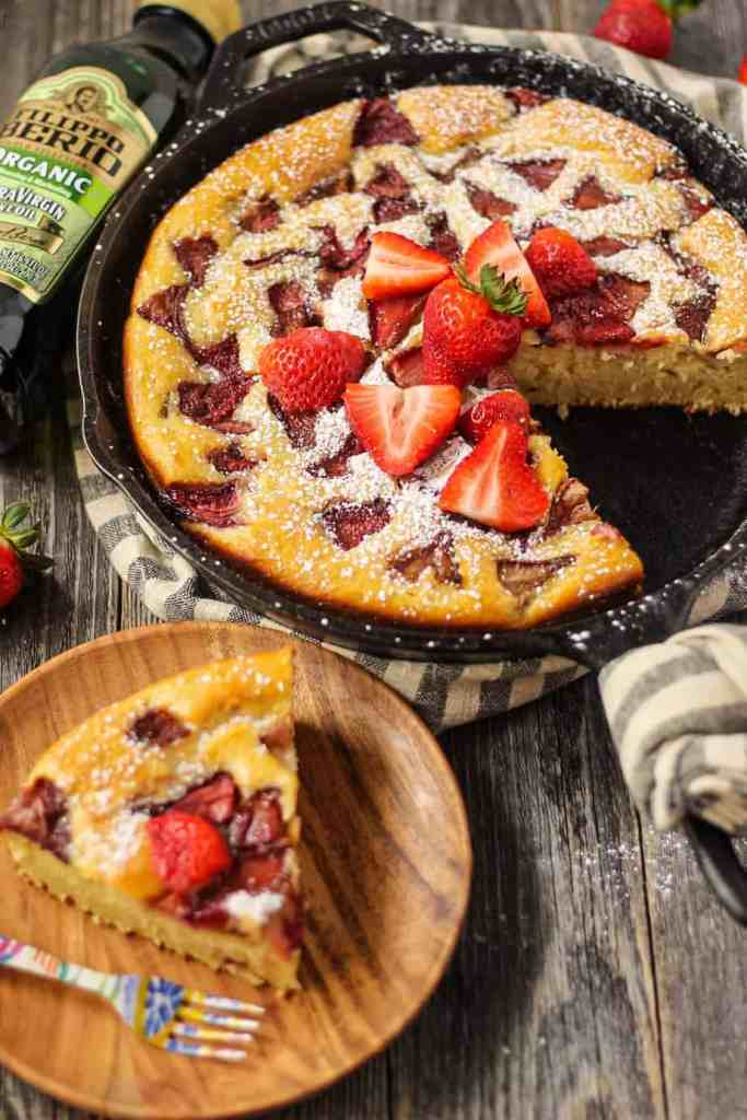 side shot of roasted strawberry skillet cake with a slice on a wooden plate.