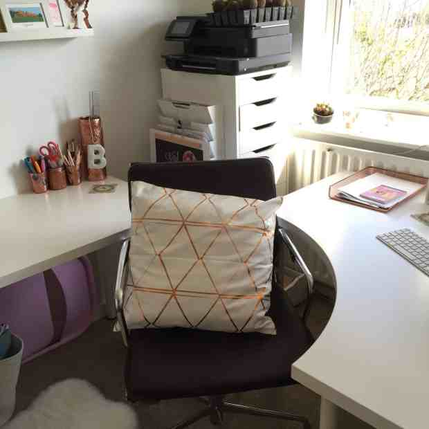 Home office with white and copper H and M cushion