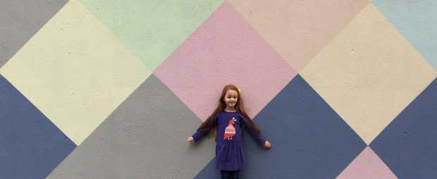 Ava standing in front of a colouiblock wall