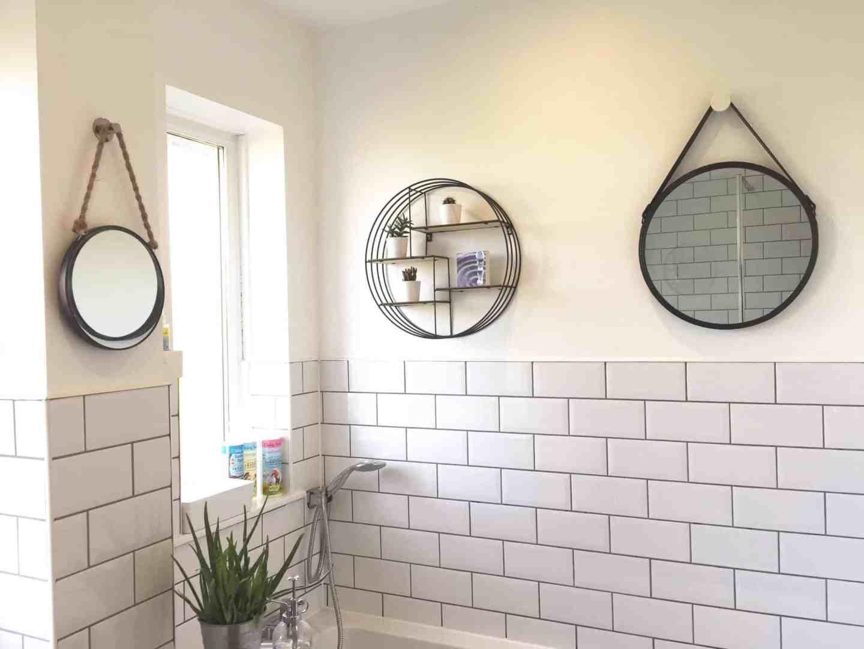 Circular black mirrors and shelving above a bath in a monochrome bathroom