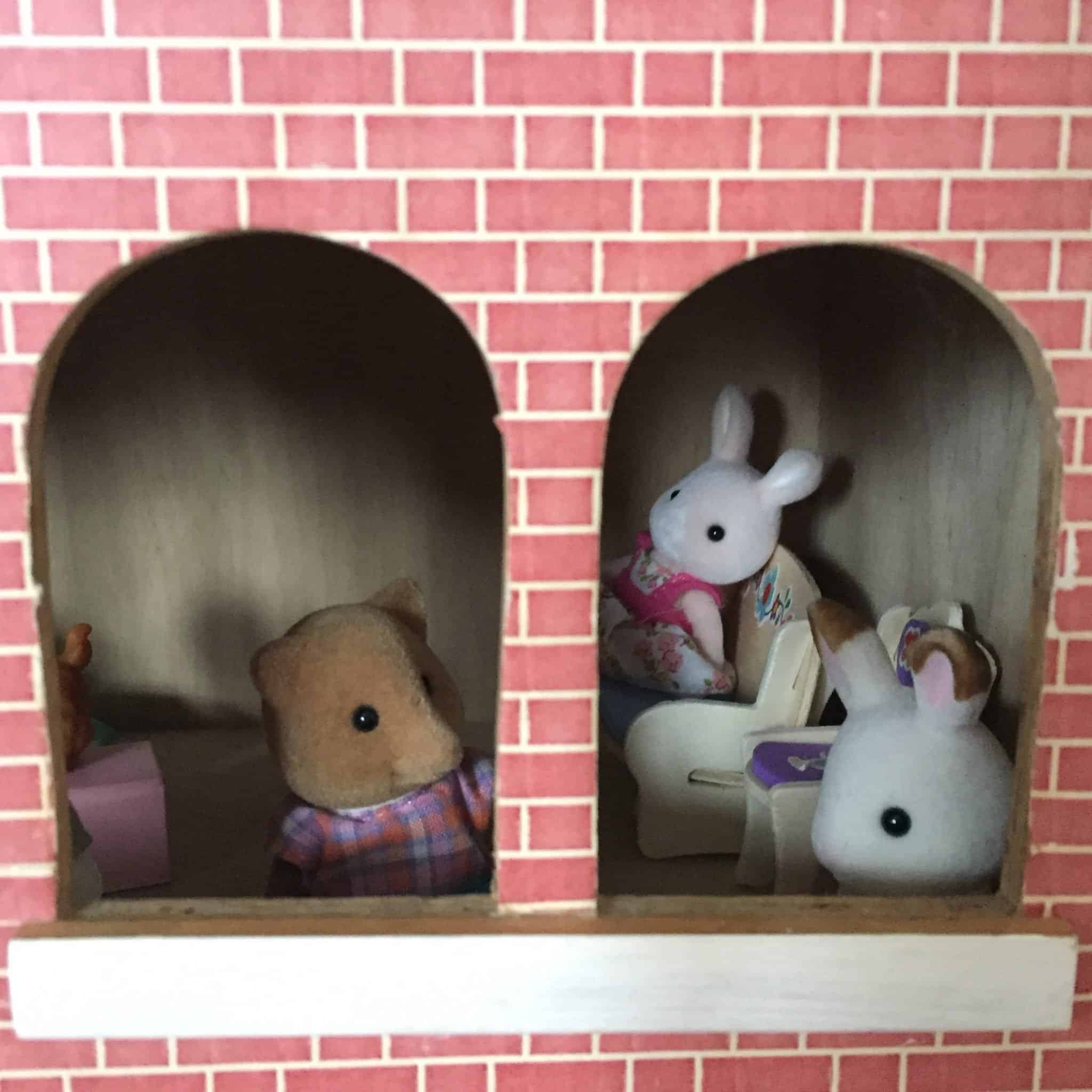 Sylvanian Families peeking out of a dolls house