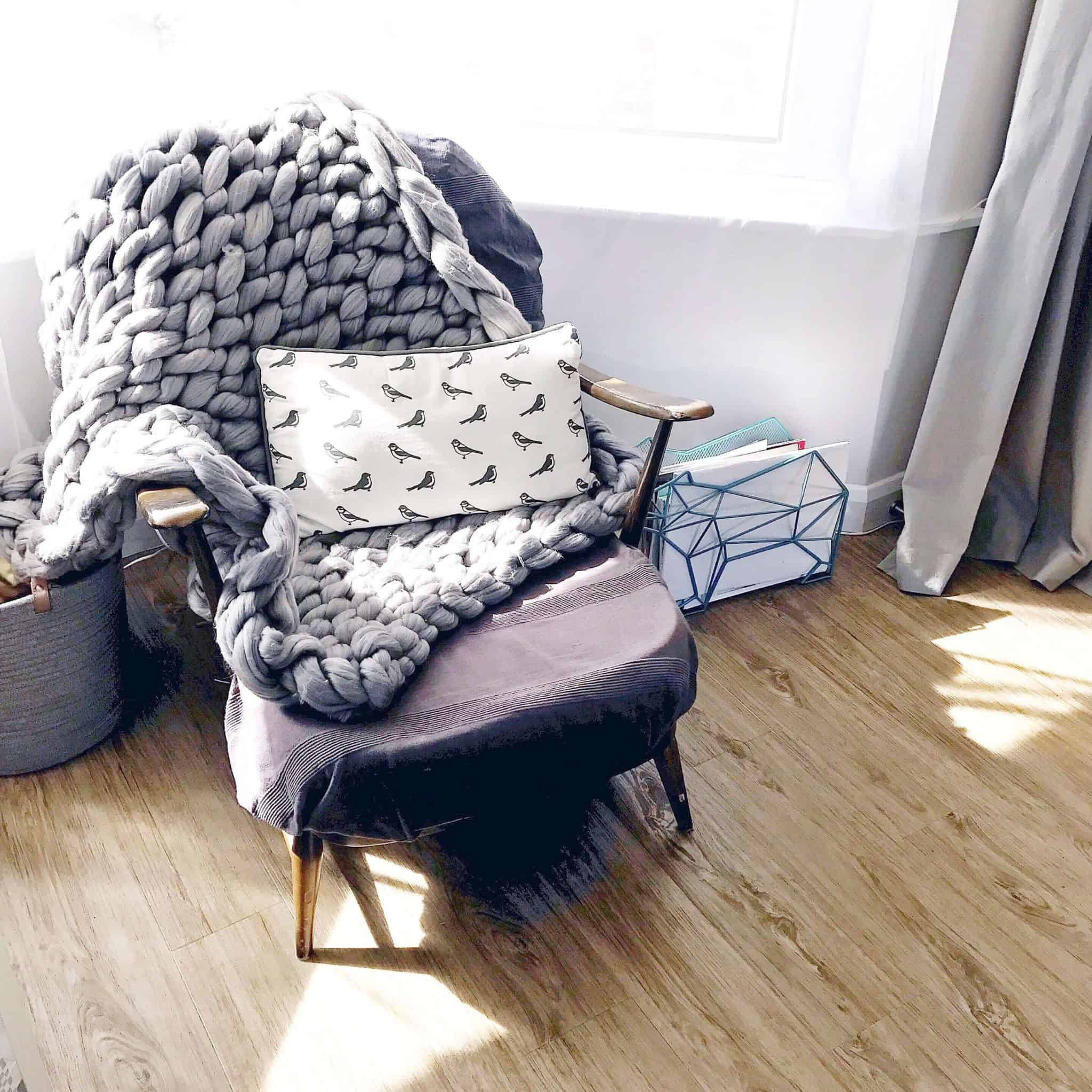 Grey arm knitted throw on an Ercol chair in a sunny lounge