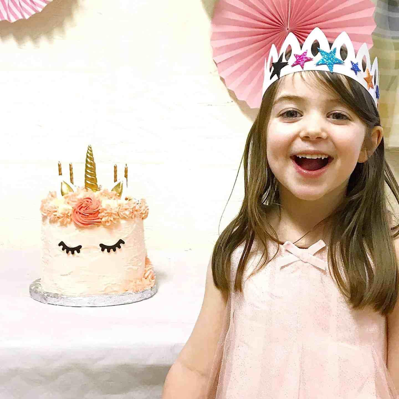 Birthday girl with her rainbow unicorn cake