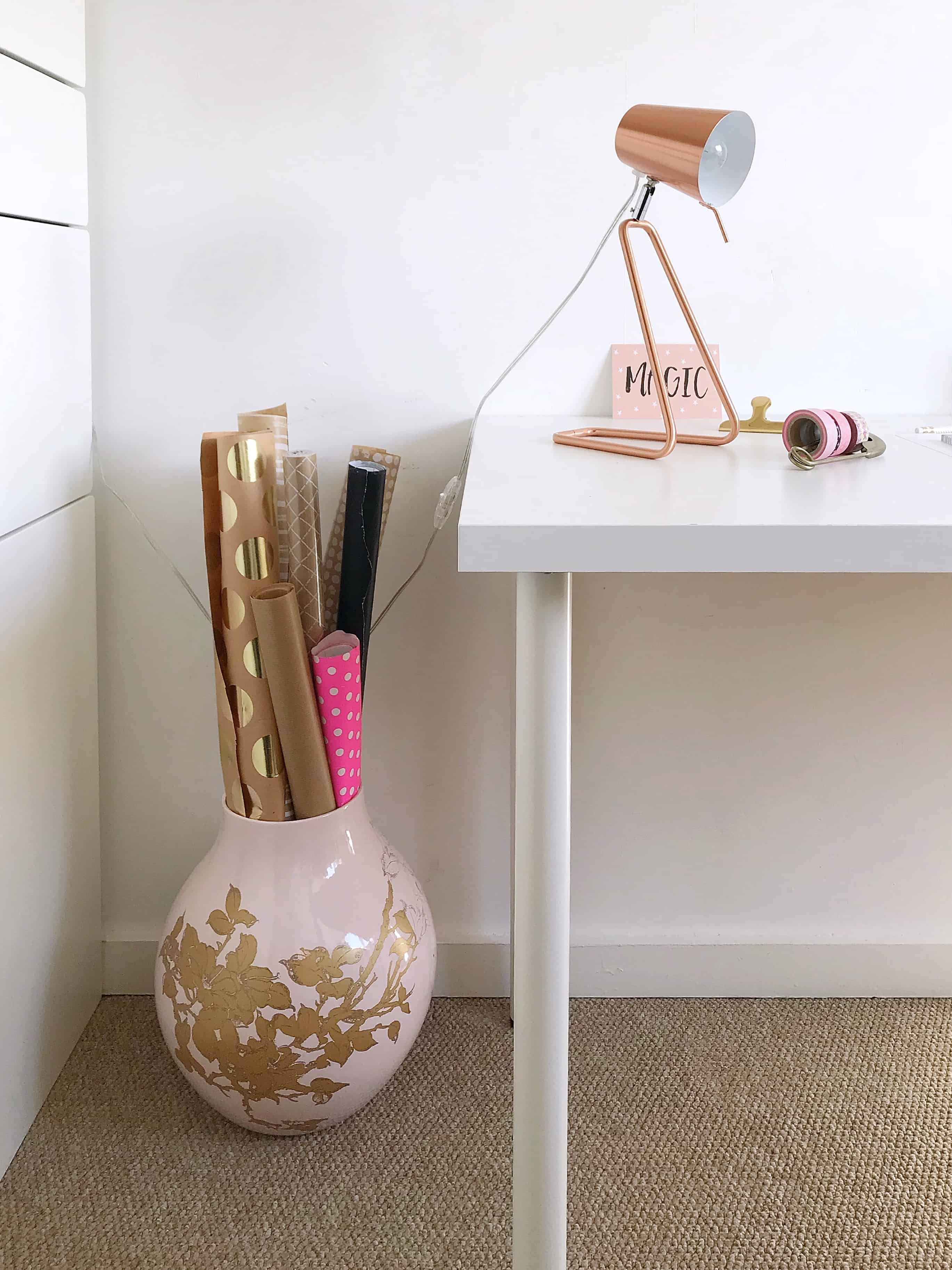 Container of wrapping paper, copper lamp and white desk