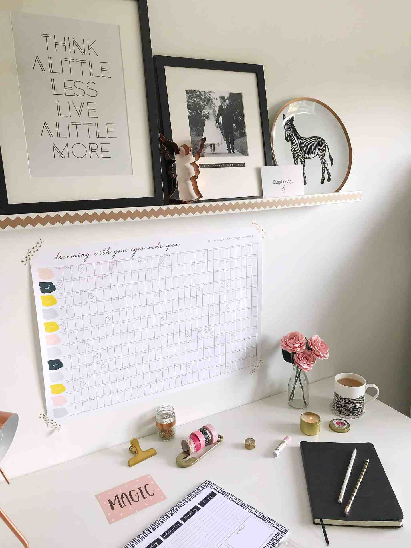 White desk with wall planner, notepooks and black and white pictures