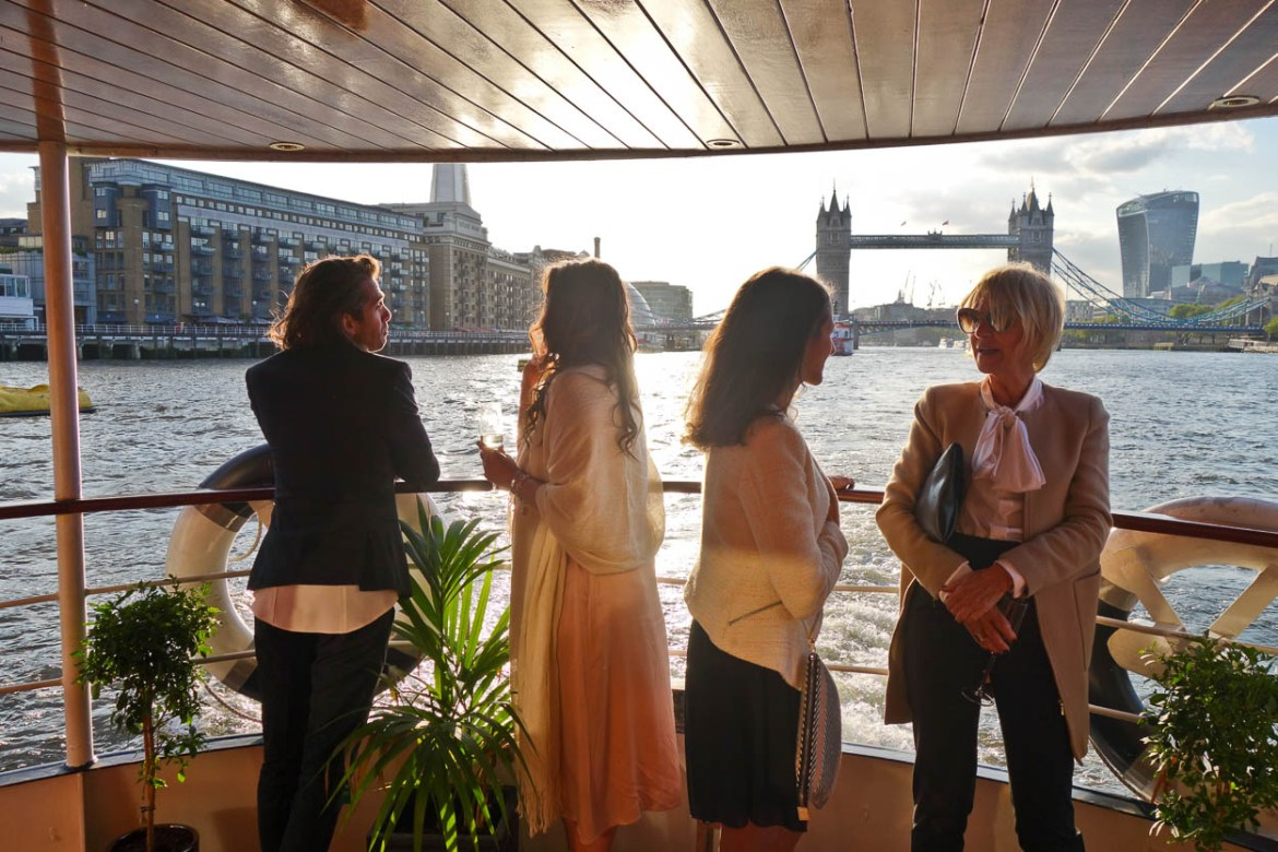 Wedding guests aboard the MV Edwardian with a backdrop of the Thames and Tower Bridge, London