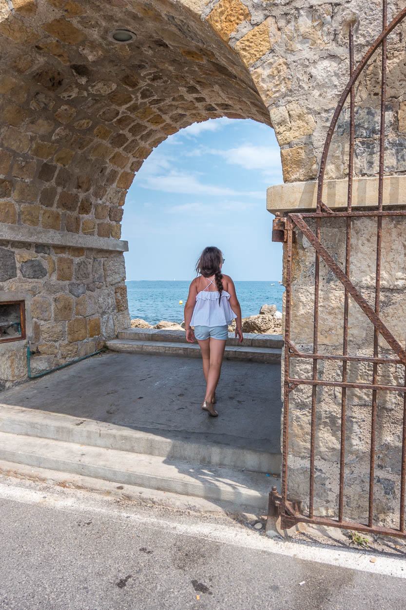 Miss France walks through the arch to the rocky beach in Antibes