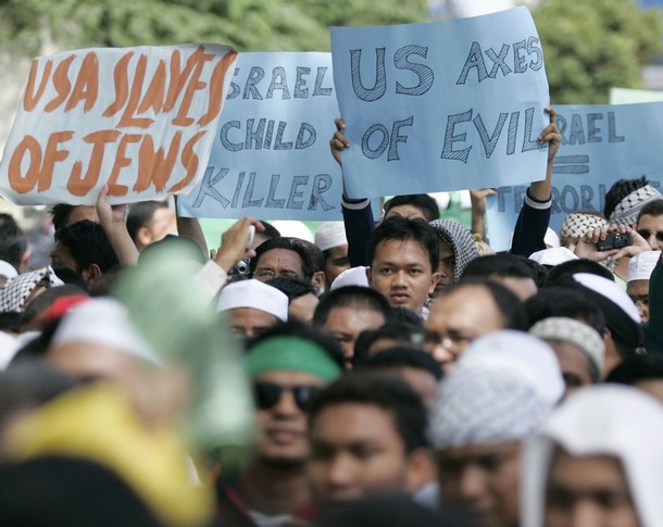 Muslim demonstrators hold placards during a demonstration in protest of Israeli aggression against Palestinians, in Kuala Lumpur December 30, 2008. REUTERS/Bazuki Muhammad (MALAYSIA)