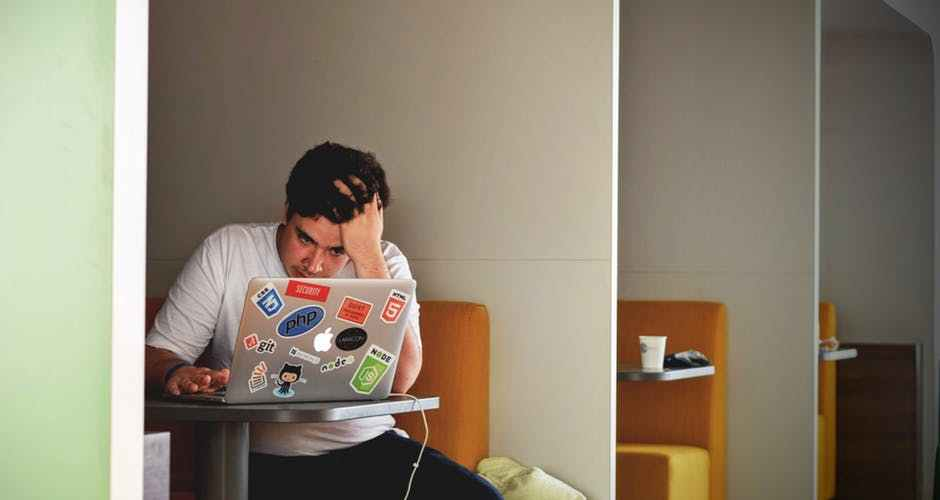 Frustrated man in white shirt using macbook pro