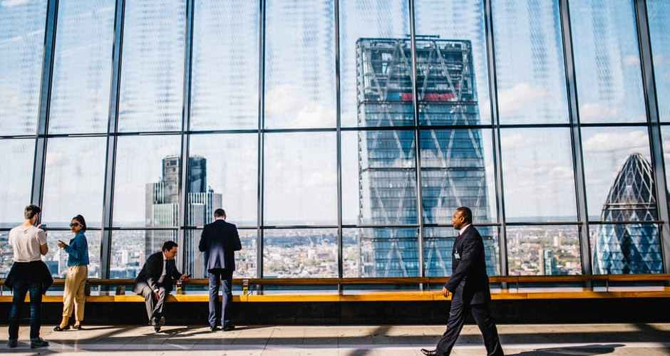 professional man walking through a large building with huge glass windows with a skyscraper in the distance
