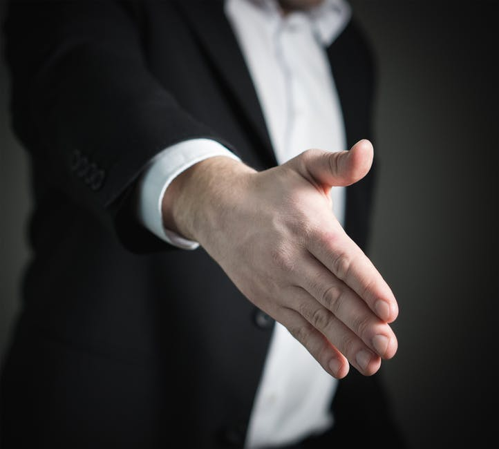 professional man reaching out to shake someone's hand