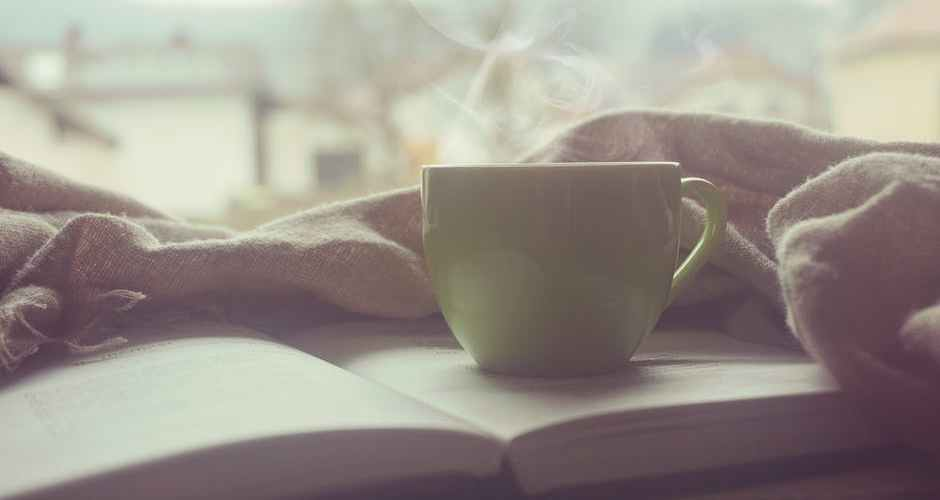 steaming cup of coffee sitting ontop of an open book