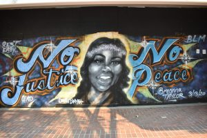 """A mural of Breonna Taylor in between the words """"No Justice No Peace."""""""