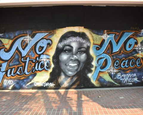 "A mural of Breonna Taylor in between the words ""No Justice No Peace."""