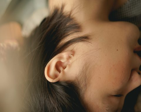 A young person lays peacefully with eyes closed
