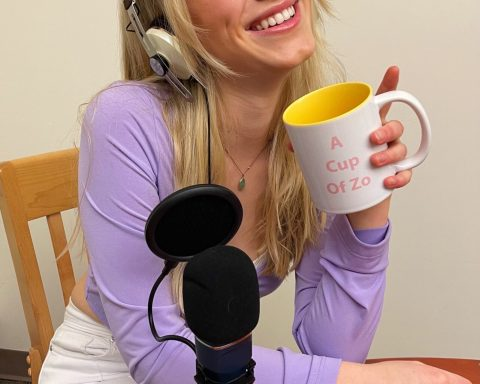 "Zoe Sanderson poses for a portrait wearing headphones, holding a mug that says ""A Cup of Zo"", with a microphone sitting on the table in front of her."