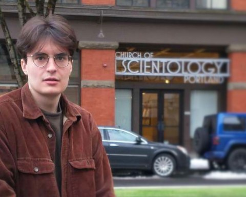 Nandrew sits in front of the Portland Branch of the Church of Scientology, looking blankly at the camera.