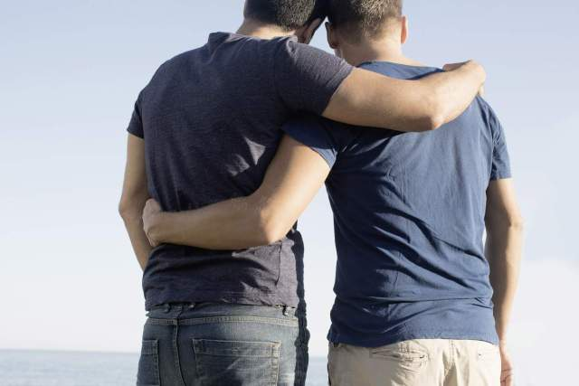 Cropped shot of mature male couple with arms around each other at coast