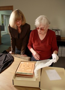 Pamela Smith Hill and Jean Coday unwrapping Pioneer Girl manuscript