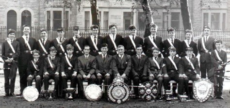 Tom Yeoman, Dougie Elmslie, Finlay Drynan, Gordon Medlow, Davy Scott, Donnie Glass, Eddie Thompson, Davy McGaffin, Alasdair Ross, Kenny Cape, Ronnie Elmslie, Junior Callaghan, Robert Wallace Sitting: Matt Recht, John Buchanan, Archie MacLean, Dan Finlay, Alex MacIver, Alex Ibell, Alastair Osborne (Company Captain), Brian May, Hughie Fulton, Willie Law