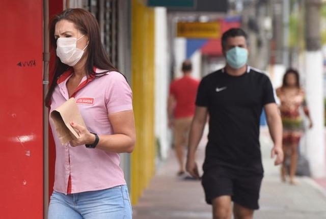 Uma foto que mostra pessoas andando de máscara na rua