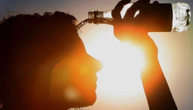 Um foto de uma pessoa se refrescando com uma garrafa de água devido ao forte calor