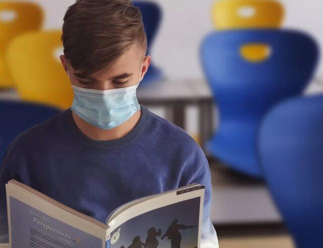 Uma foto de um estudante na sala de aula usando máscara enquanto lê um livro